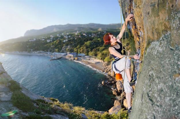 Donna atletica che sale una scogliera sporgentesi contro il fondo scenico della costa di mare. estate.