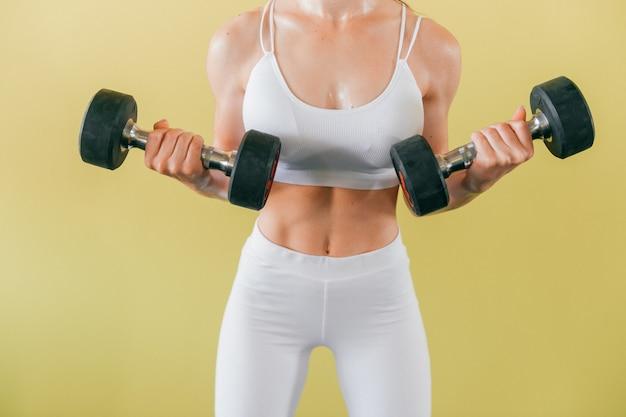 Donna atletica culturista con manubri. bella ragazza castana con i muscoli che sollevano i pesi