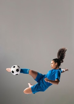 Donna atletica della foto a figura intera che dà dei calci alla palla