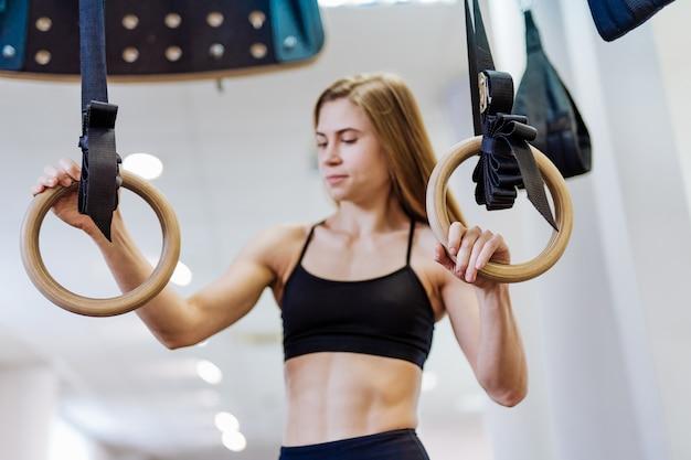 Donna atletica di esercizio muscolare che tiene gli anelli relativi alla ginnastica e che sorride nella palestra.