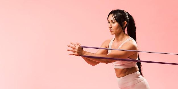 Donna atletica in attrezzatura della palestra che tira la banda di resistenza