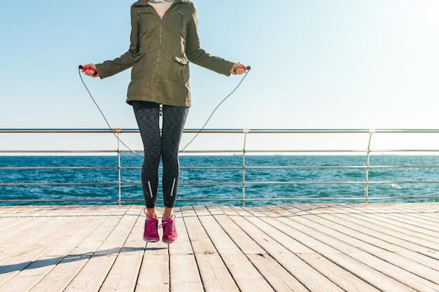 Donna atletica in giacca e scarpe da ginnastica salta la corda al mattino sullo sfondo del mare
