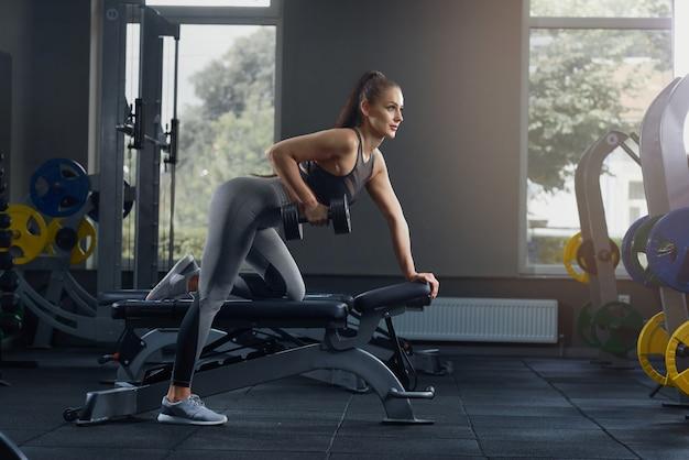 Donna atletica sexy che pompa i muscoli con le teste di legno alla palestra.