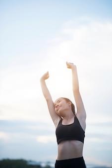 Donna atletica sorridente felice con le armi stese