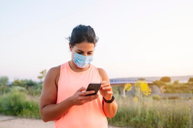 Donna atletica utilizzando il suo smartphone con maschera facciale all'aperto