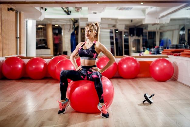 Donna attiva attiva di forma fisica di bella forma sexy che si siede su una palla di forma fisica con le gambe aperte e che esamina la macchina fotografica nella palestra.