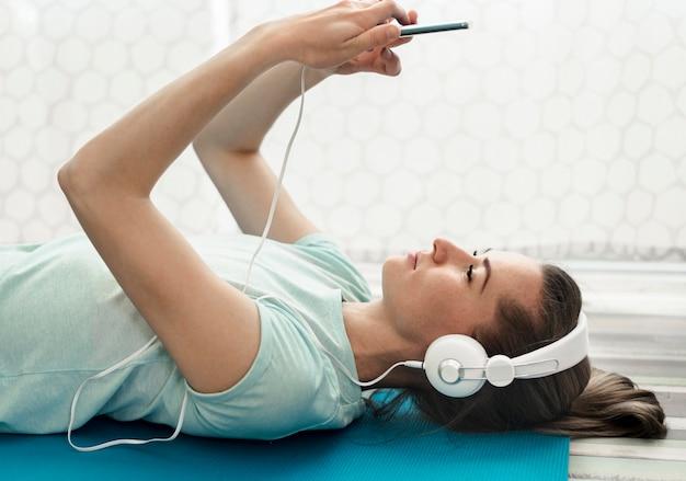 Donna attiva del primo piano che ascolta la musica