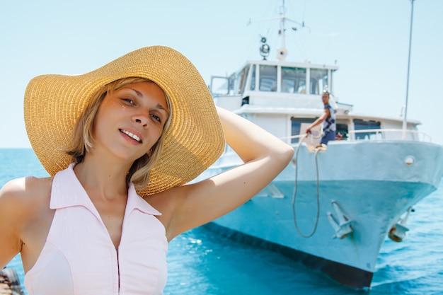 Donna attraente bionda sorridente che posa in cappello
