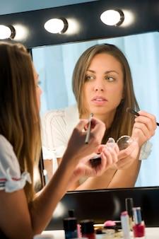 Donna attraente che applica il suo trucco in uno specchio