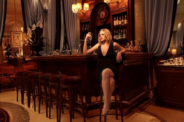 Donna attraente che beve da solo in una barra