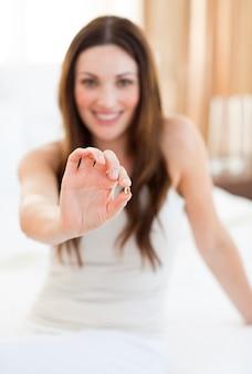 Donna attraente che cattura una pillola che si siede sul letto
