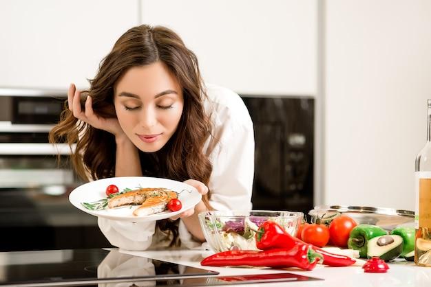 Donna attraente che cucina pasto delizioso da pesce e verdure in cucina