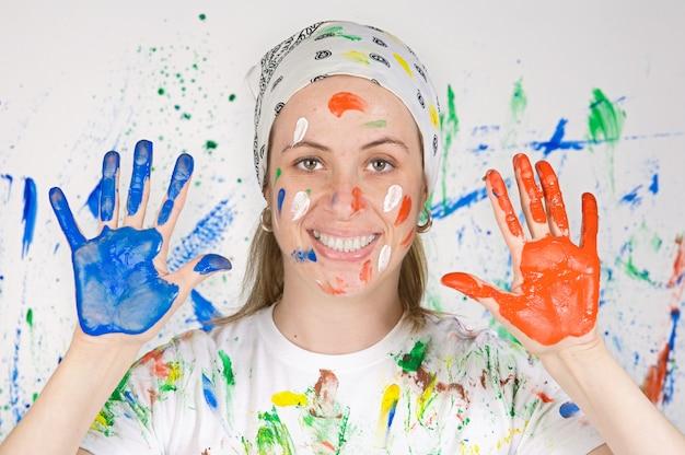 Donna attraente che dipinge lo sfondo di molti colori