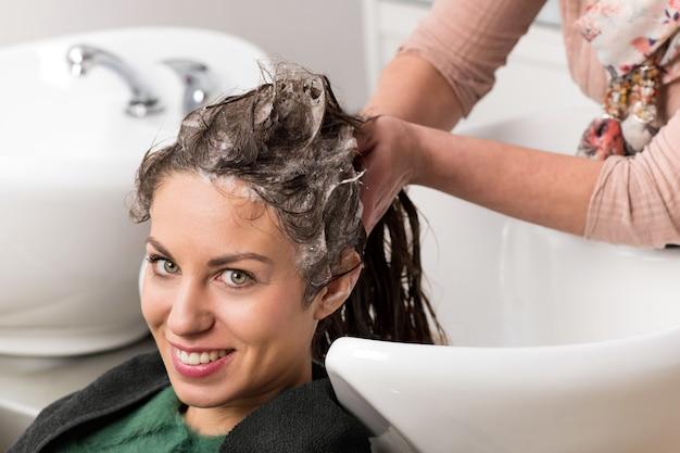 Donna attraente che fa lavare i suoi capelli