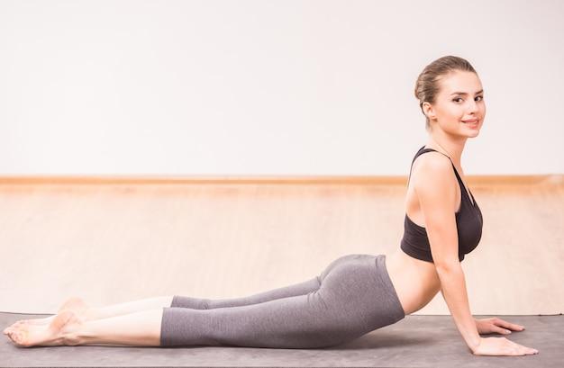 Donna attraente che fa posizione ascendente di yoga del cane sulla stuoia.