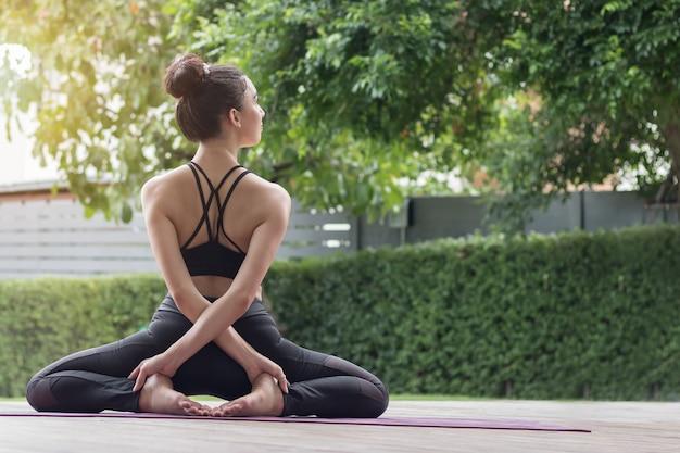 Donna attraente che gioca yoga per la sua buona salute