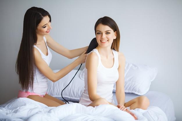 Donna attraente che lecca a sua sorella mentre pettina i capelli
