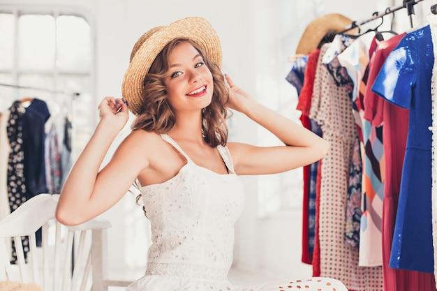 Donna attraente che prova su un cappello. buon shopping estivo.