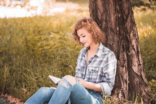 Donna attraente che si appoggia sull'albero e recita libro in giardino pubblico