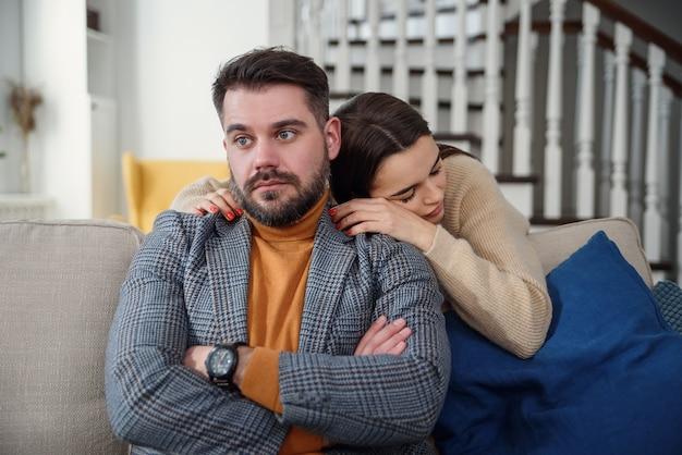 Donna attraente che si scusa con l'uomo frustrato dopo il litigio, il fidanzato dubbioso ignora, la fidanzata sentirsi in colpa, chiedendo di perdonarla, chiedendo scusa, ammette errore, rimpianto, coppia che ha problemi