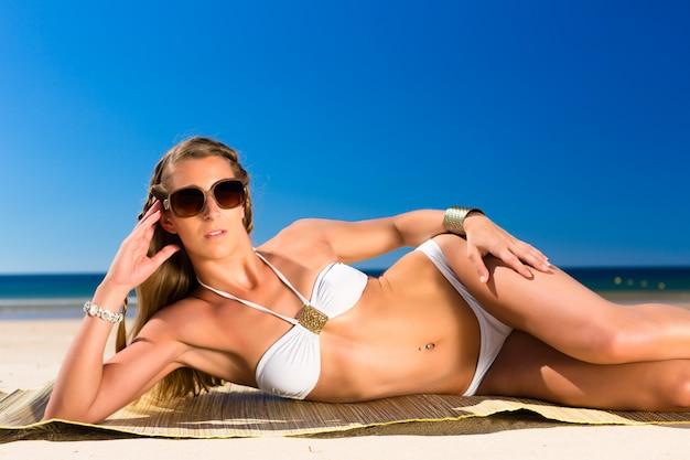Donna attraente che si trova al sole sulla spiaggia