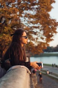 Donna attraente che utilizza smartphone all'aperto nel parco