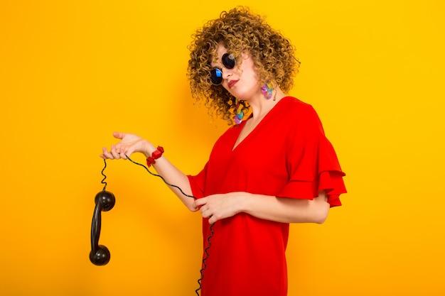 Donna attraente con brevi capelli ricci con il telefono