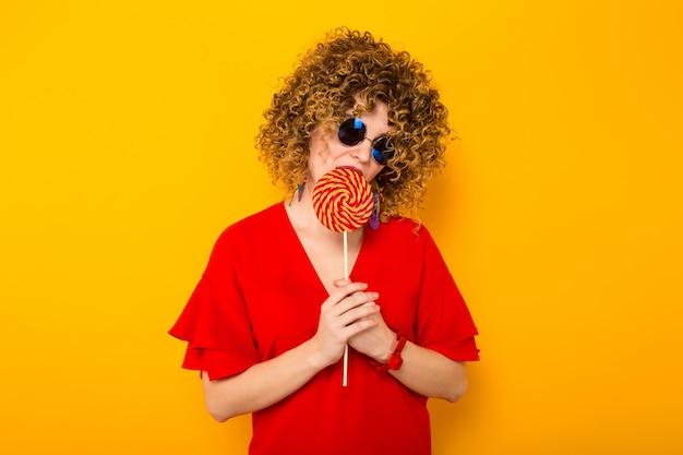 Donna attraente con capelli corti ricci con caramelle