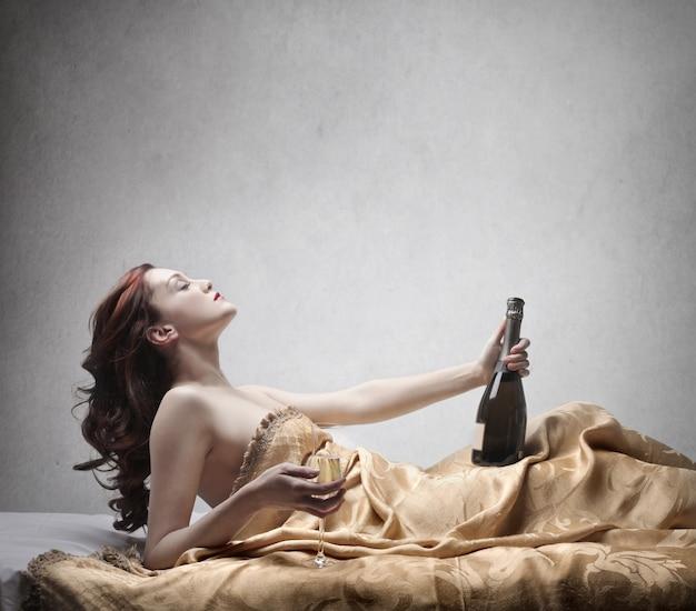 Donna attraente con champagne a letto