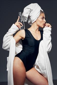 Donna attraente con costume da bagno e accappatoio, asciugamano in testa e bottiglia d'acqua in mano