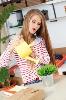Donna attraente con erba con annaffiatoio