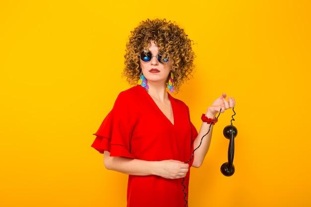 Donna attraente con i capelli corti ricci con il telefono