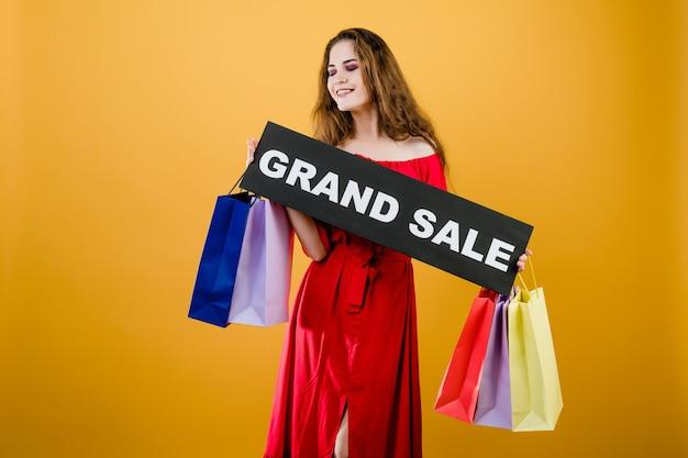 Donna attraente con il grande segno di vendita e sacchetti della spesa variopinti isolati sopra giallo