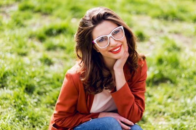 Donna attraente con labbra carnose, occhiali da vista, giacca rossa, acconciatura ondulata che si siede sull'erba verde nel parco soleggiato di primavera e sorridente