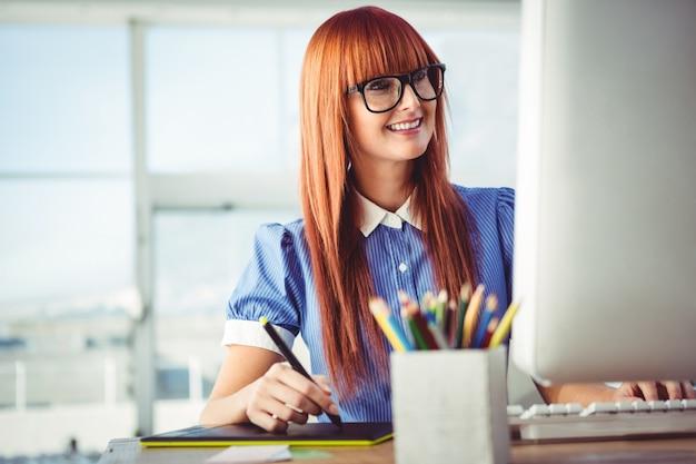 Donna attraente dei pantaloni a vita bassa che utilizza la tavola dei grafici nel suo ufficio
