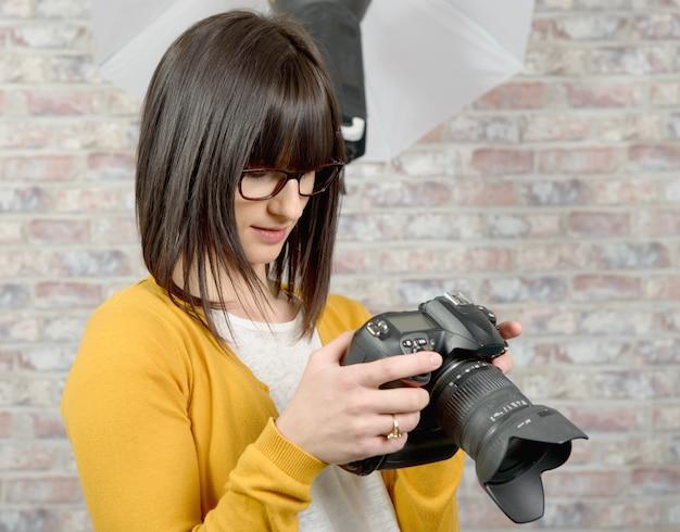 Donna attraente del brunette con la macchina fotografica