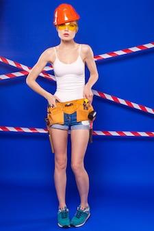 Donna attraente del costruttore in camicia bianca, cintura del costruttore, casco, occhiali del costruttore, pantaloncini jeans e risate