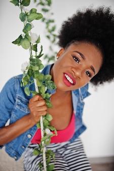 Donna attraente dell'afroamericano con usura dei capelli afro sulla giacca di jeans e gonna, posato nella stanza bianca sull'altalena. modello nero alla moda.