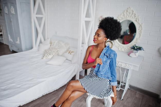 Donna attraente dell'afroamericano con usura dei capelli di afro sulla giacca dei jeans e della gonna, proposta alla stanza bianca. modello nero alla moda.