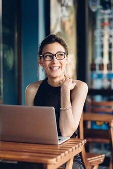 Donna attraente di affari che lavora al suo computer portatile