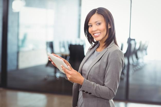Donna attraente di affari che tiene compressa digitale