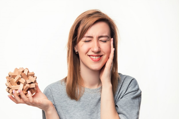 Donna attraente di affari di 24 anni che sembra sconcertante con il puzzle di legno.