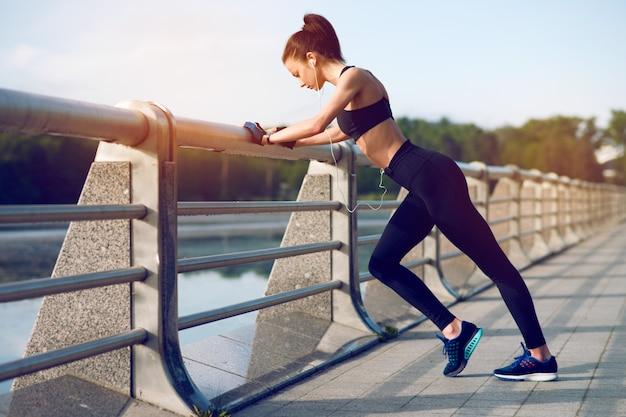 Donna attraente e forte che allunga prima della forma fisica e che ascolta la musica con le cuffie sul lago di estate. concetto di sport. uno stile di vita sano