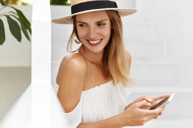Donna attraente e sognante allegra con pelle sana e sorriso piacevole legge informazioni su smart phone o messaggi nei social network, utilizza internet ad alta velocità. persone, comunicazione, estate