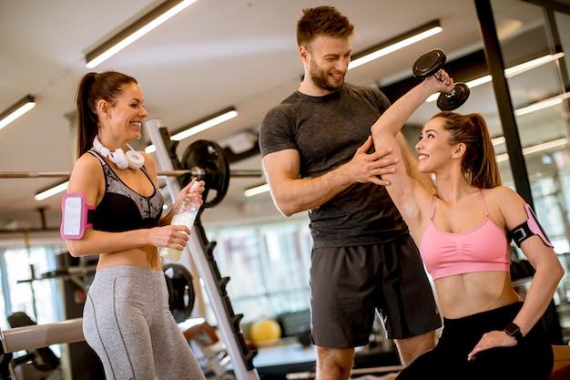 Donna attraente e un personal trainer con allenamento con i pesi in palestra