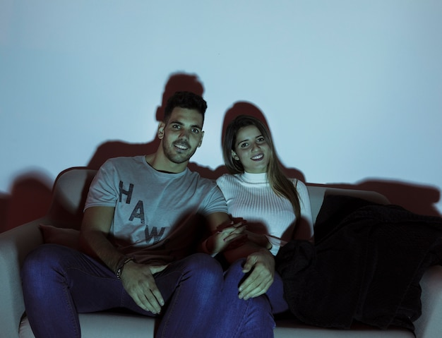 Donna attraente e uomo bello guardare la tv sul divano in camera oscura
