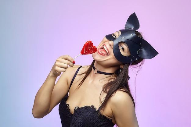Donna attraente in maschera di gatto che lecca caramelle