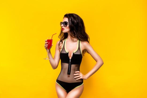 Donna attraente in monokini nero con bicchiere di bevanda rossa. reto