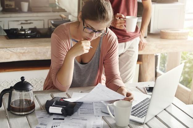 Donna attraente in occhiali con penna seria e concentrata che guarda mentre si compilano documenti, si calcolano le bollette, si tagliano le spese della famiglia, si cerca di risparmiare per fare grandi acquisti