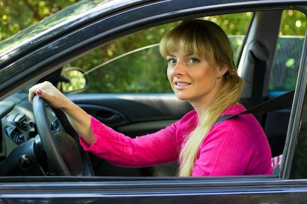 Donna attraente in rosa godendo la corsa nella sua auto